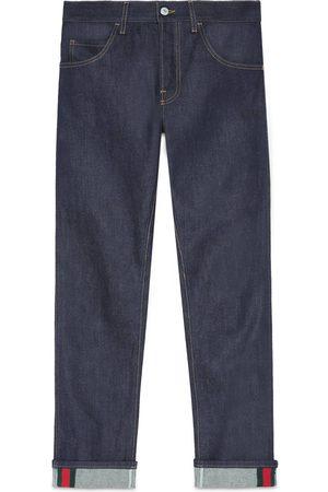 Gucci Herren Stretch - Dunkelblaue Jeans mit abgeschrägtem Bein und Webstreifen