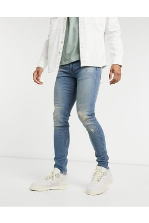Levi's – Enge, schmal zulaufende Jeans in dunkler Tapster Distressed Advanced-Vintage-Waschung